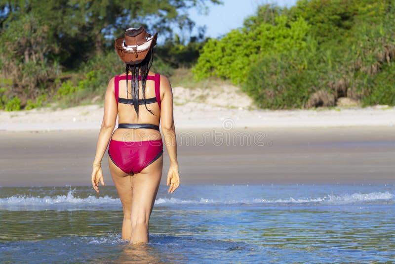 Cramoisi de femme et de bikini avec la promenade de chapeau sur la plage images libres de droits