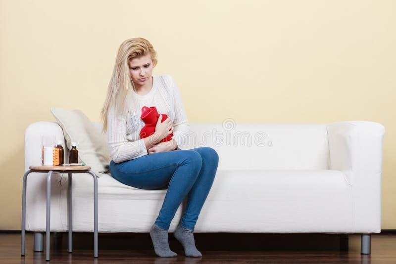 Crampes d'estomac de sentiment de femme se reposant sur le cofa photographie stock