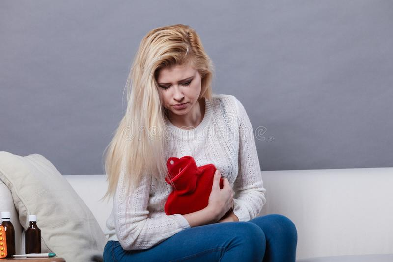 Crampes d'estomac de sentiment de femme se reposant sur le cofa photo libre de droits