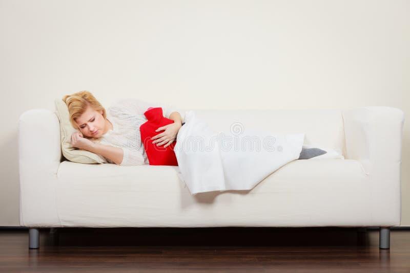 Crampes d'estomac de sentiment de femme se trouvant sur le cofa images stock