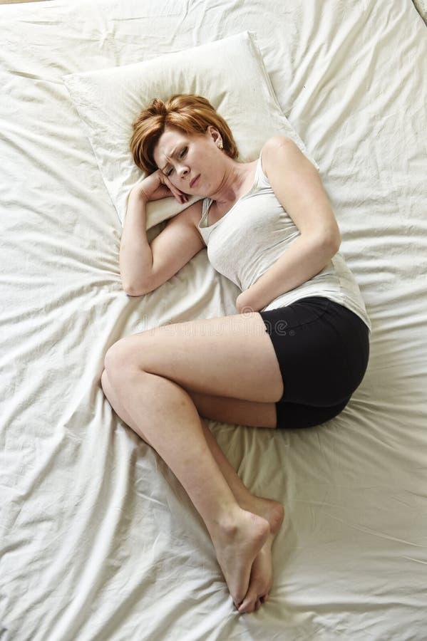 Crampes d'estomac de souffrance de jeune belle femme sur le ventre tenant le ventre avec ses mains en douleur de période photos libres de droits