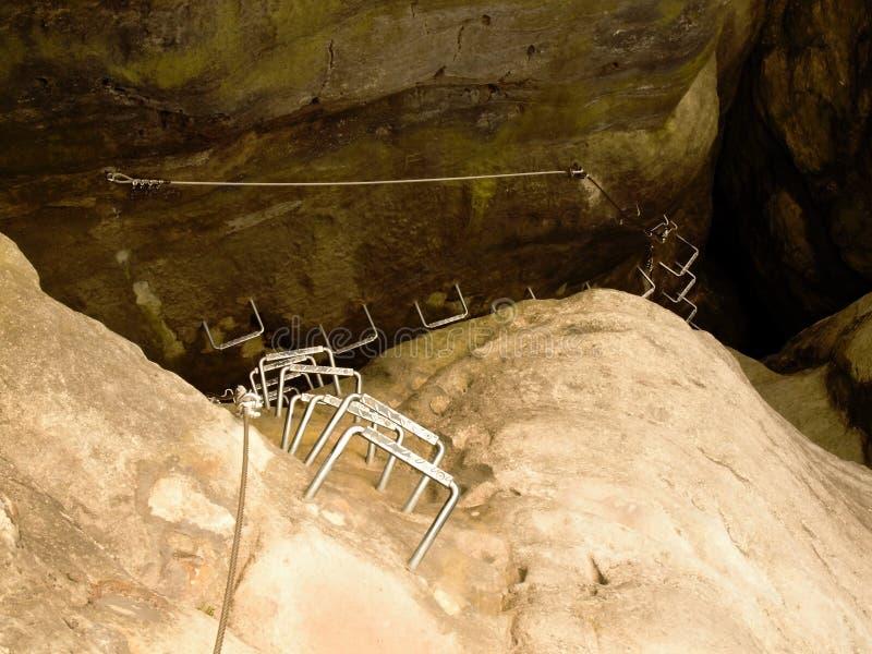 Crampes de fer dans la roche, échelle de touristes de ferrata Repassez la corde tordue fixe dans le bloc par les crochets instant image stock