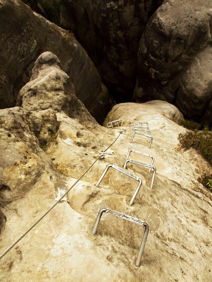 Crampes de fer dans la roche, échelle de touristes de ferrata Repassez la corde tordue fixe dans le bloc par les crochets instant photographie stock libre de droits