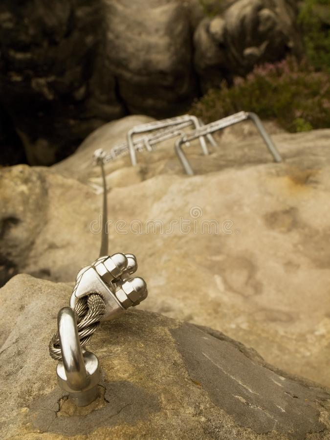 Crampes de fer dans la roche, échelle de touristes de ferrata Repassez la corde tordue fixe dans le bloc par les crochets instant images stock