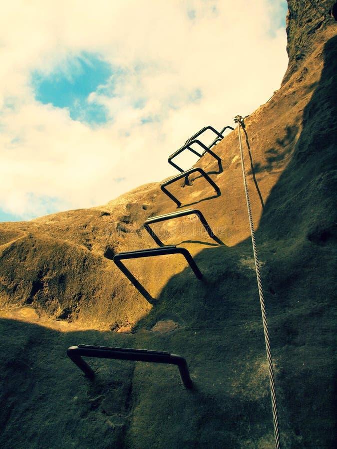 Crampes de fer dans la roche, échelle de touristes Repassez la corde tordue fixe dans le bloc par les crochets instantanés de vis image libre de droits