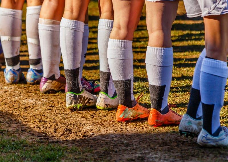 Crampons, chaussettes et jambes dans la boue photos stock