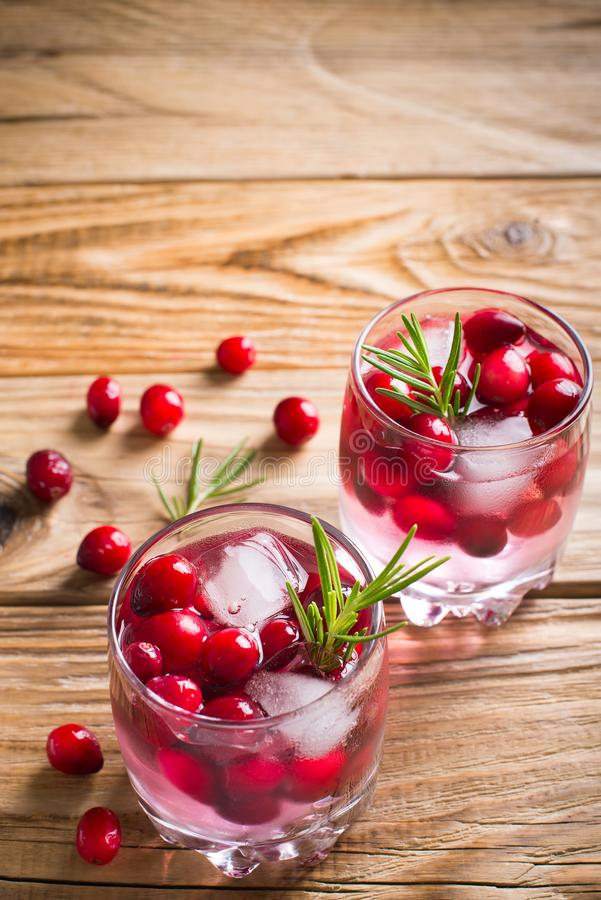 Cranberries cocktails with ice? berries and rosemary stock photos