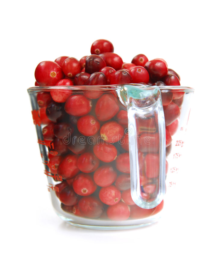 Cranberries in a cup. Fresh red cranberries in a glass measuring cup on white background royalty free stock photo