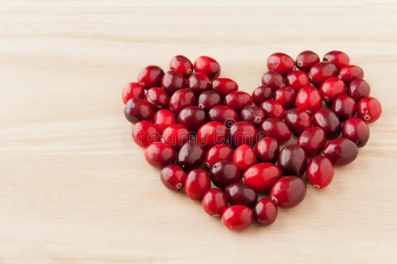 Cranberries in heart shape on wooden board. royalty free stock photography