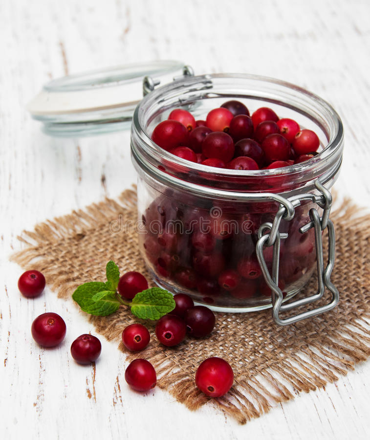 Cranberries. Jar with fresh cranberries on a old wooden background royalty free stock photography