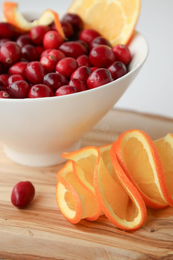 Cranberries and juicy orange slices royalty free stock images