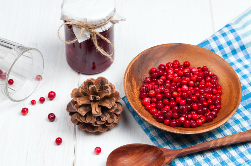 Cranberries in wooden bowl with spoon and jam in jar on white surface royalty free stock photos