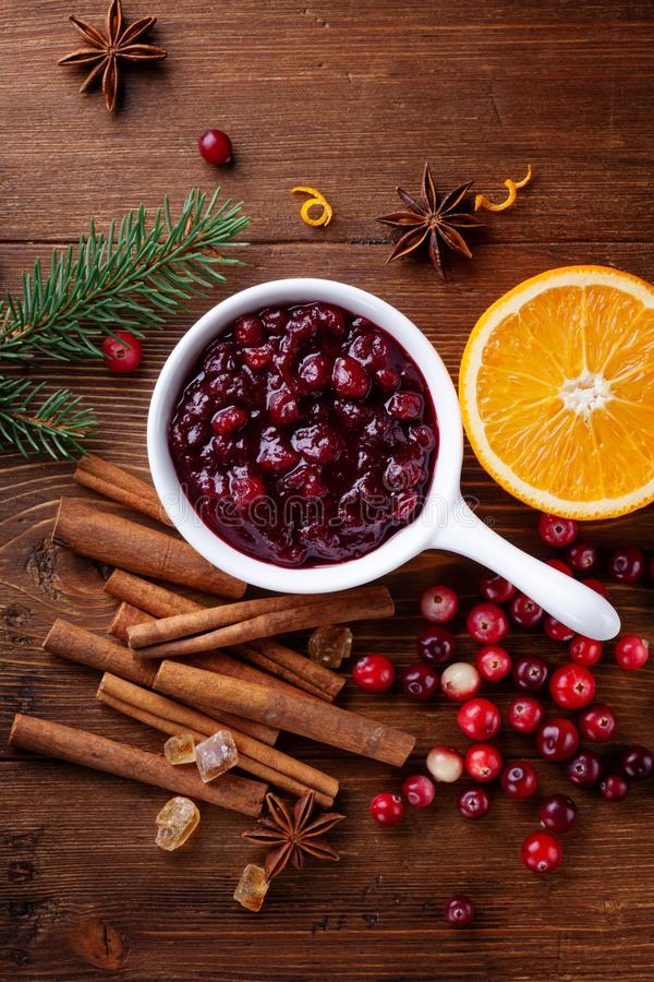 Cranberry sauce in ceramic saucepan with ingredients for cooking decorated with fir tree for Christmas or Thanksgiving day. On rustic kitchen table from above stock photo