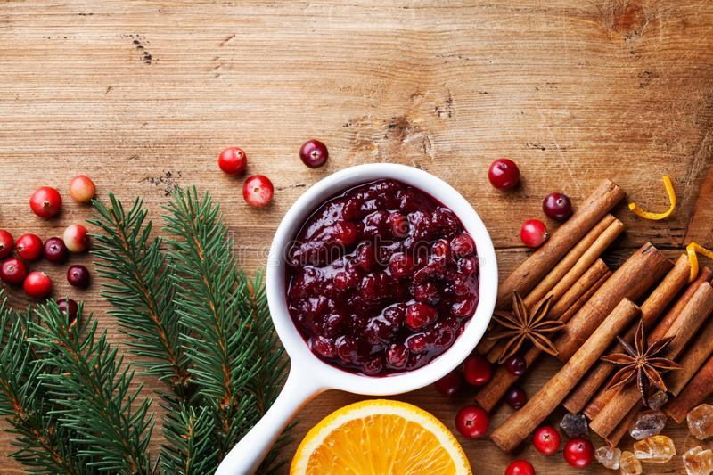 Cranberry sauce in ceramic saucepan with ingredients for cooking decorated with fir tree for Christmas or Thanksgiving day on wood. En kitchen table. Top view stock photography