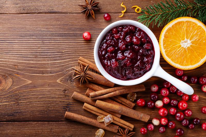 Cranberry sauce in ceramic saucepan with ingredients for cooking decorated with fir tree for Christmas or Thanksgiving day on wood. En kitchen table. Top view royalty free stock images