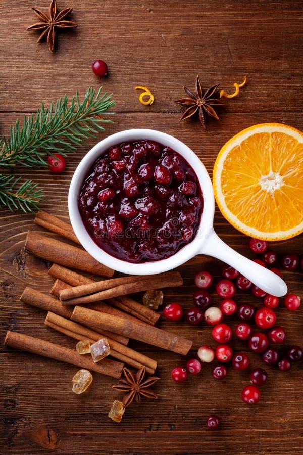 Cranberry-Sauce in keramischer Saucepan mit Zutaten zum Kochen mit Tannenbaum für Weihnachts- oder Thanksgiving-Tag dekoriert stockfoto