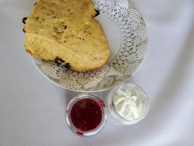 Cranberry scone raspberry jam and cream on a white tablecloth royalty free stock photos