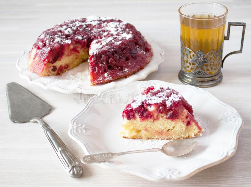 Cranberry tart pie cake piece, plate, spoon, tea glass, cup holder, spatula on white wooden table stock image