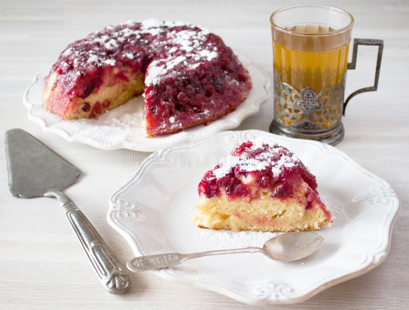 Cranberry tart pie cake piece, plate, spoon, tea glass, cup holder, spatula on white wooden table royalty free stock photo
