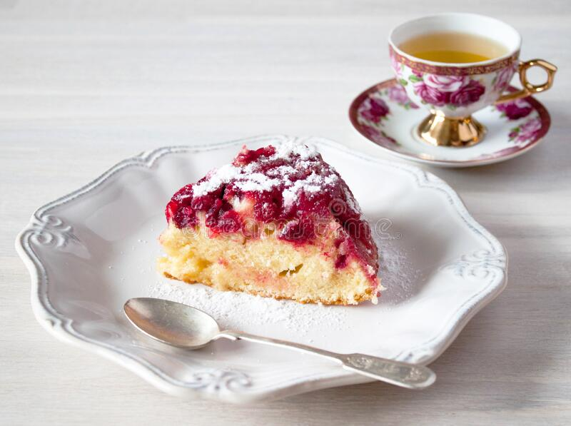Piece of cranberry tart, pie, cake on plate, tea spoon, cup of tea on white wooden table backgound stock images