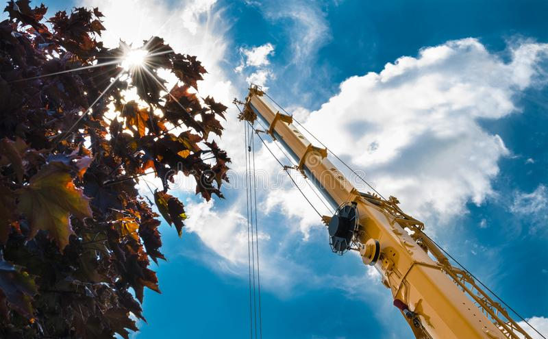 Crane arm during work at heights on building. Romantic shot from below with tree, sky, clouds and sun rays stock images