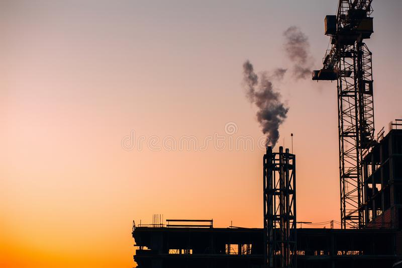 Crane and building construction site with pipe with smoke on background of sunset sky. Industrial landscape with silhouettes of c. Ranes over sunset. Pollution royalty free stock photos