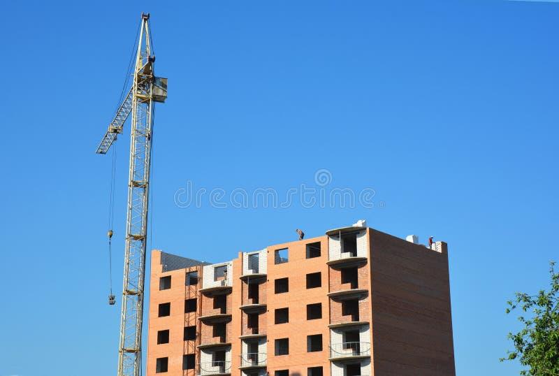 Crane a construção com os contratantes de construção na parte superior Conceito do crescimento econômico fotografia de stock