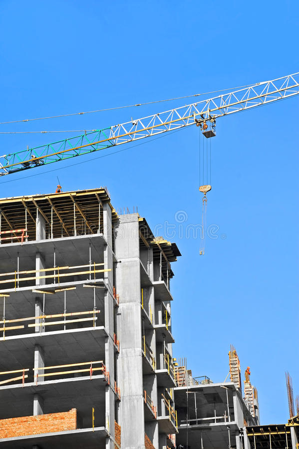 Crane and construction site. Crane and building construction site against blue sky stock images