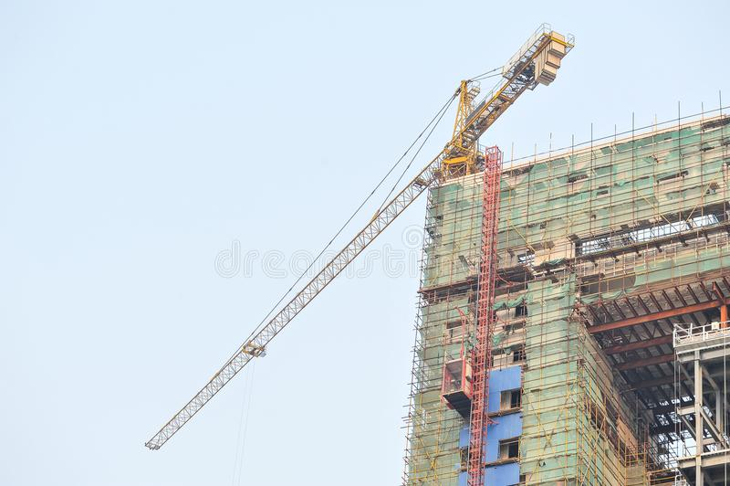 A crane on a construction site. A tall building, a crane on a construction site royalty free stock photography