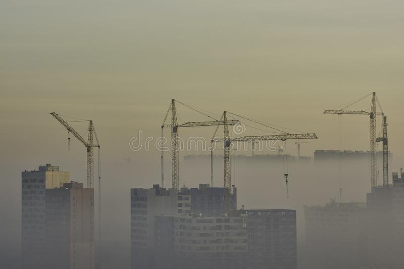Crane and construction site in urban smog stock photography