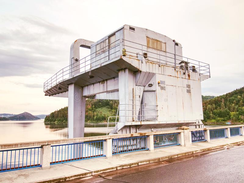 Crane for control water gate on dam. Crumbling dam across the river. A crossing over the dam road, weir, upper, view, tune, trees, transport, service, reservoir royalty free stock image
