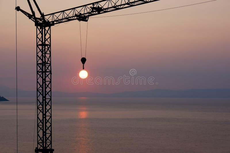 Crane el sol de cogida del gancho durante puesta del sol sobre el mar foto de archivo libre de regalías