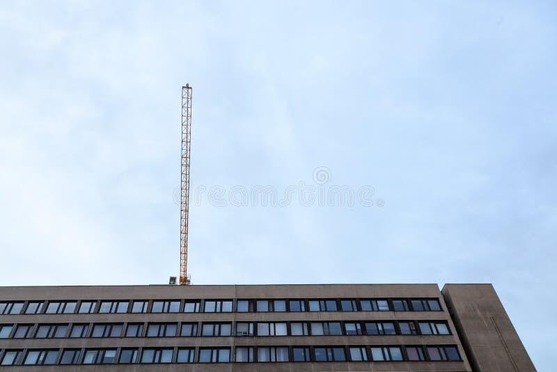 Crane en un emplazamiento de la obra sobre un edificio de oficinas de 70 ` s del estilo socialista actualmente en la renovación e foto de archivo