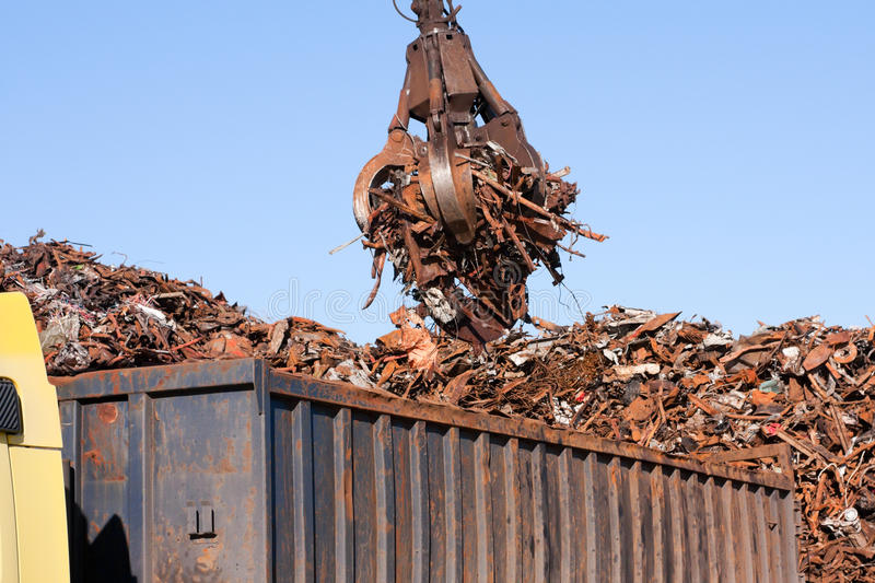 Crane grabber loading a Truck with metal scrap. Crane grabber loading a Truck with metal rusty scrap in the dock stock images