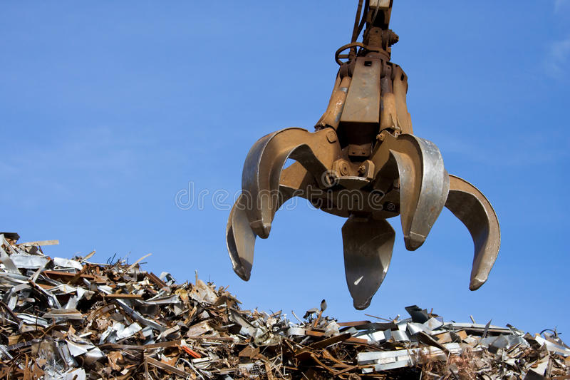 A crane grabber up on the metal heap stock photo