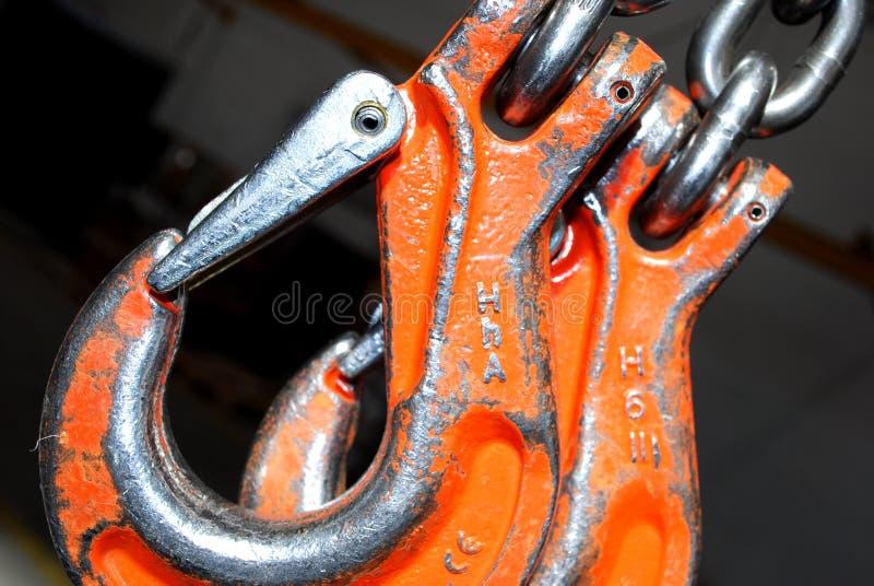 Crane hook. Orange Double crane hook with iron chain stock photos