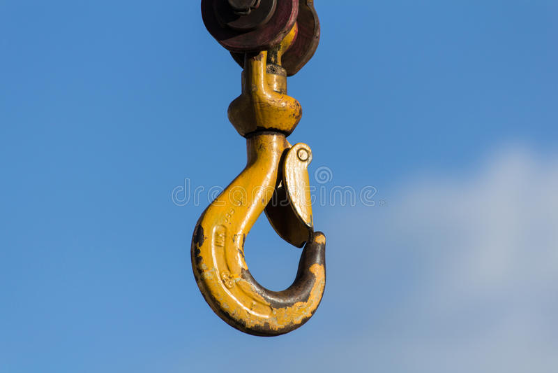 Crane Hook jaune sur un fond bleu photo stock