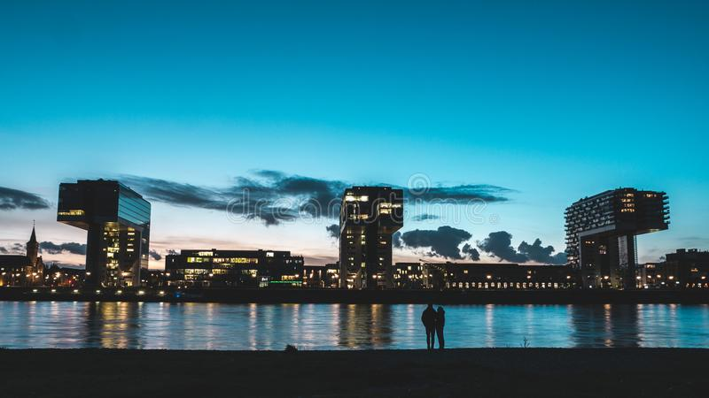 Crane Houses in Cologne, Germany with silhouette of couple royalty free stock image
