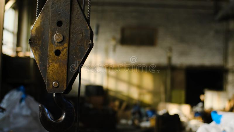 Crane inside warehouse. Stock footage. Old rusty crane hook suspended on background of abandoned warehouse of industrial stock image