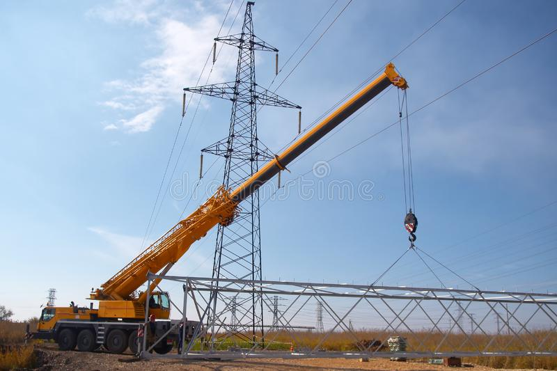 A crane installs a high voltage power line in an industrial suburb royalty free stock images