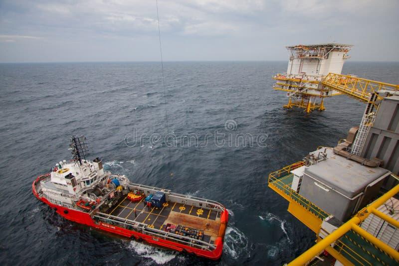 Crane la operación con el barco de la fuente, transferencia del cargo. foto de archivo