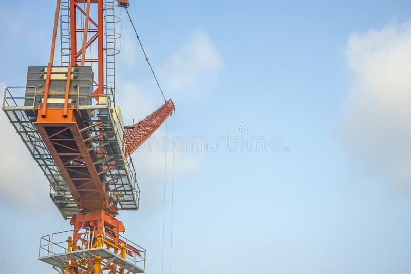 Crane lift orange in the blue sky.  royalty free stock images
