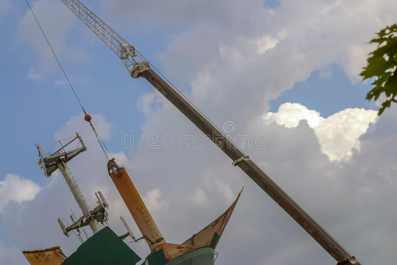 Crane lifting off sections of an old steel water tower. Dismantling of an old water tower on a beautiful summer`s day by torches and a large crane. This water stock photo