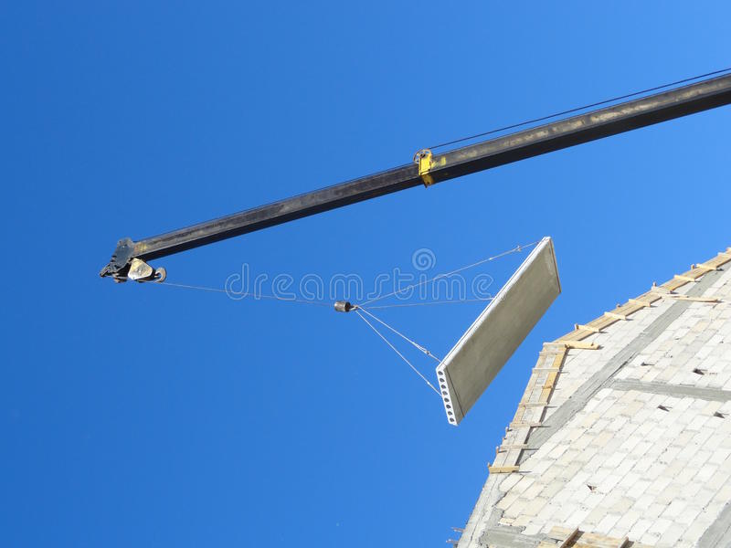 Crane lifting a part of a roof stock photography