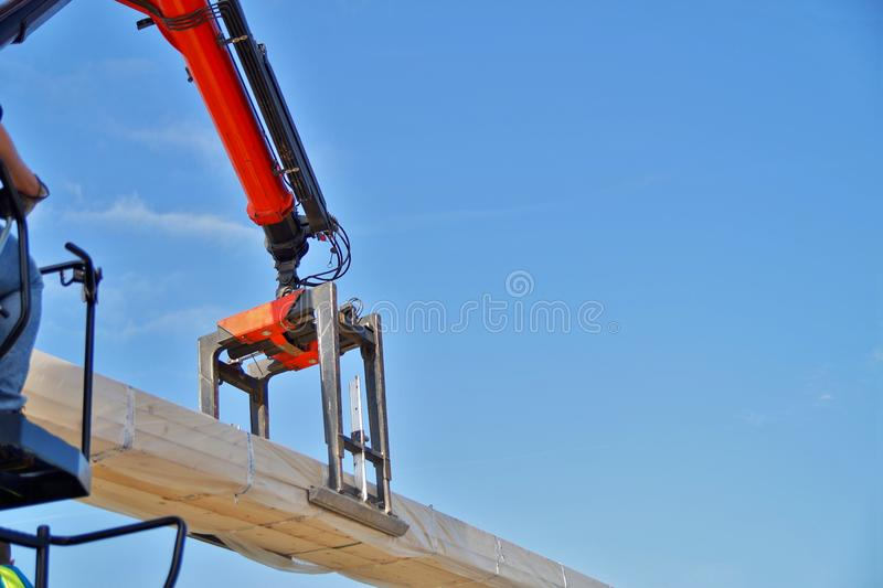 Crane lifting whole wooden beams. Workers raise the logs with a crane. New construction framework. stock photos