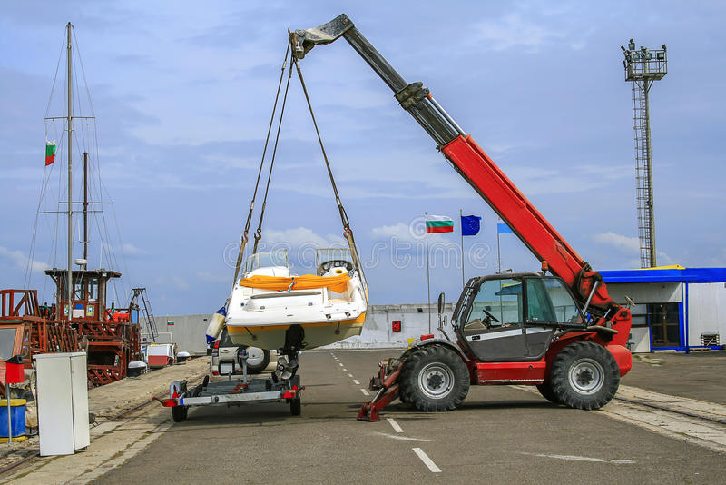 Crane lifts a boat stock photo