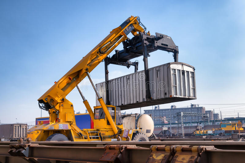 Crane lifts a container loading a train stock images