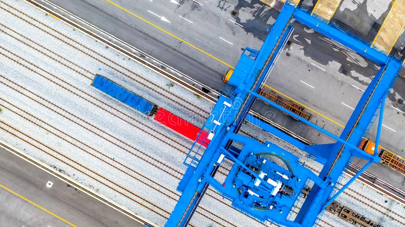 Crane loading container on a train, Rails in container port, Aerial view.  royalty free stock photos