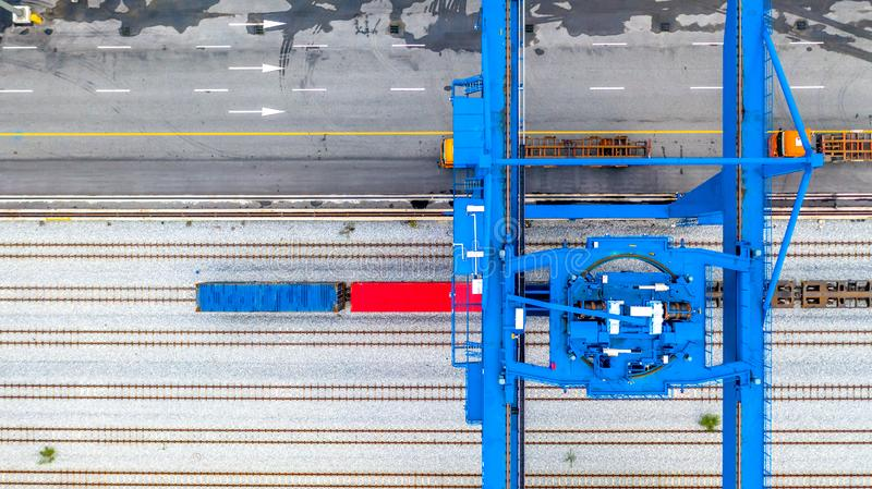 Crane loading container on a train, Rails in container port, Aerial view.  stock photo