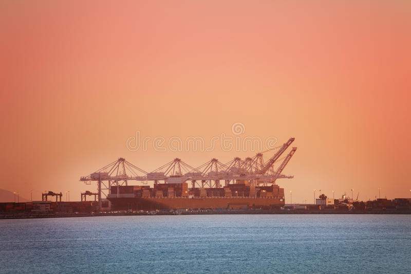 Crane loading containers on barge, Long Beach, USA. Crane bridge loading containers on barge at Long Beach shipping port at dusk, California, USA royalty free stock images